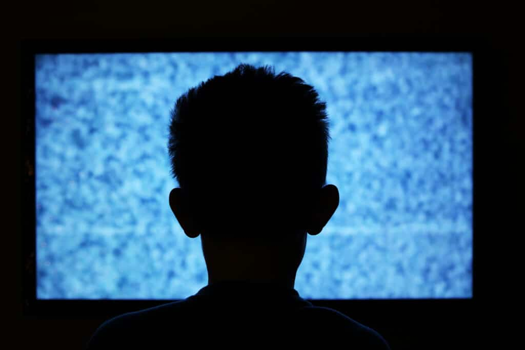 virtual autism header image. child watching static on tv.